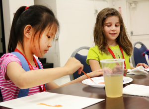 Victoria, 7, and Isabella, 7, paint pictures in the FACE Center's cafeteria for the Picasso Art camp on June 17. Jake McMahon / Pioneer