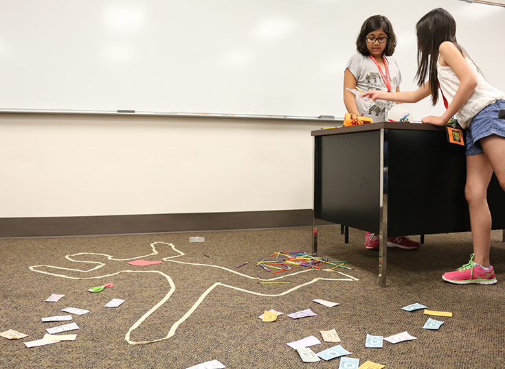 Shireen, 11, and Olivia, 10, examine evidence in the Crime Solver camp on June 17. Jake McMahon/Pioneer