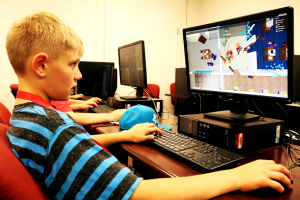"Zach, 11, plays a video game called ""Roblox"" in the Humanoid Robotics camp on June 17. Jake McMahon / Pioneer"