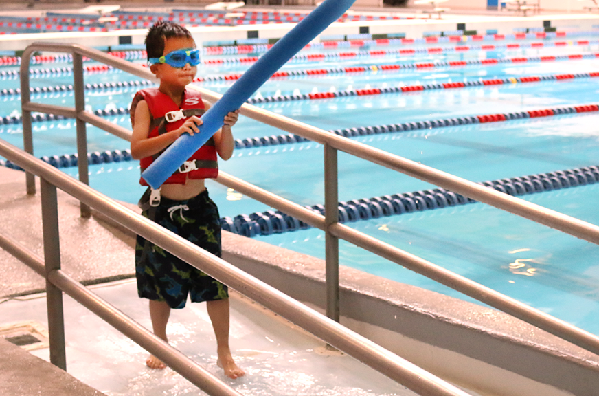 "Andrew, 7, walks toward OCCC's pool with a pool noodle, ready to take the plunge. After lunch, the Musical Theater  ""Yee Haw!"" class got a swim break to cool off.     Jake McMahon/Pioneer"