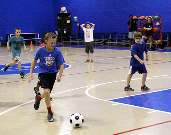 Collin and Austin, both 10, watch as their fellow camper Danny, 12, kicks a soccer ball downfield in OCCC's gym on June 10. The boys are enrolled in an OCCC summer recreational camp. JAKE MCMAHON/PIONEER