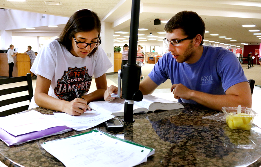 "Medicine health and society major Devin Pinoroc and industrial engineering and management major Spencer Jones station themselves at a table in the main building on June 24. ""We're studying physics,"" Jones said. ""We have a test tomorrow. It's definitely challenging.""  Jake McMahon/Pioneer"