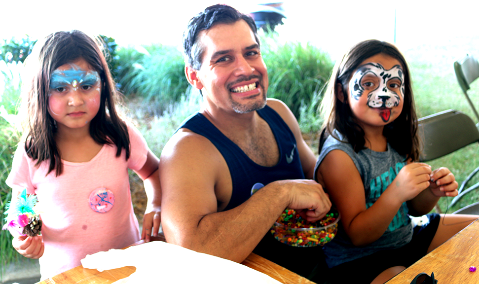 Grace, 5, and Brileigh, 7, make necklaces with their father Damon