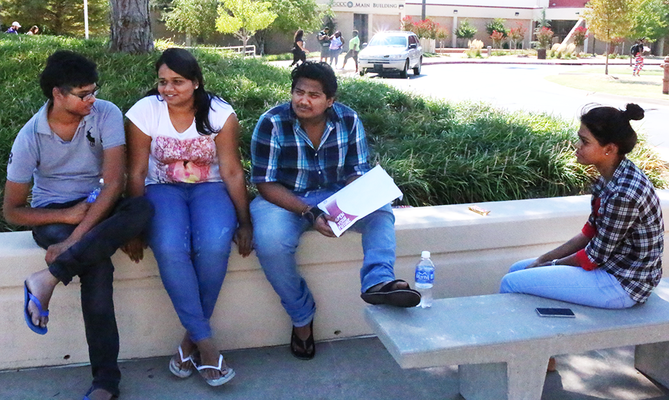 students sit in the shade near Keith Leftwich Memorial Library