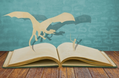 A paper cut of a dragon and a child coming out of a book.