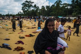 A Rohingya woman grips a bag of rice, while others search for food among donated articles of clothes. Pioneer Photo by Rahul Chakraborty.