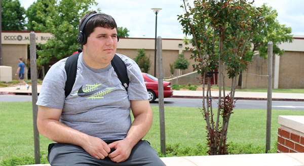 "Cartography major Jacob Smith sits outside of OCCC's Main Building on June 16. ""I'm waiting for a ride, listening to Three 6 Mafia,"" Smith said. ""I love hip hop."" Jake McMahon/Pioneer"
