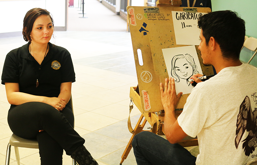 Ashlynn Chumard sits for a caricature by caricature artist Hector Lopez