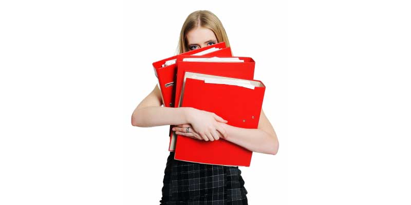 An overworked businesswoman holding many binders
