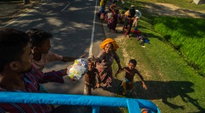 In Myanmar, people are starving and homeless. A young girl seeks a safe haven under a cloth tent. Refugees swarm a truck in search of food while a young boy looks on. Trucks filled of bags of rice wait to be unloaded. Refugees search for food among piles of useless donated clothes while children race for candy being thrown from a truck.  Pioneer Photos by Rahul Chaktaborty and Shantonu Paul
